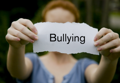 A girl holding out the word bullying on a slip of paper